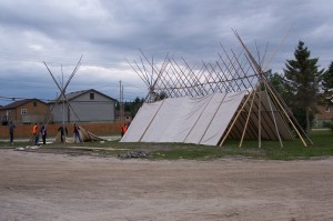 picture of traditional housing being erected for gathering of the peoples